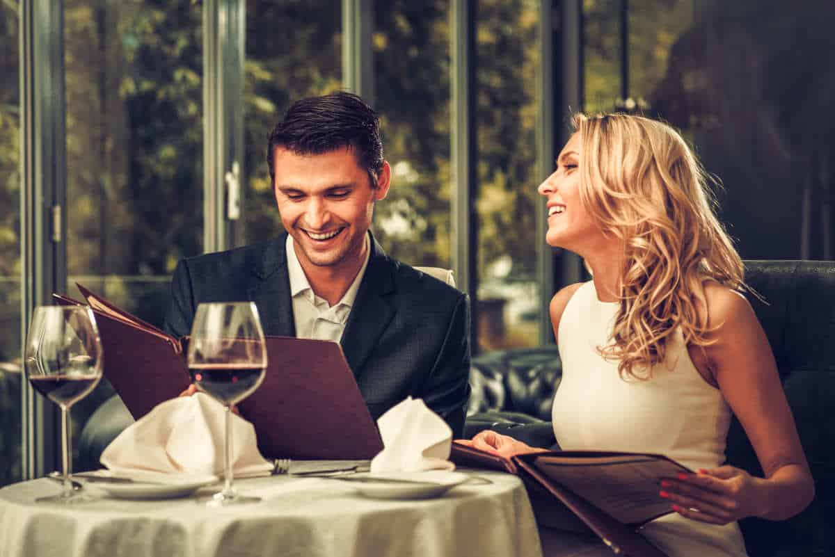 Cheerful couple with menu in a restaurant | How Many Ways Can You Say Happy Birthday to a Techie? | Happy Birthday Techie