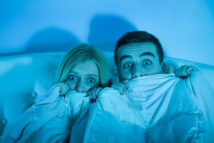 Frightened couple watching horror movie