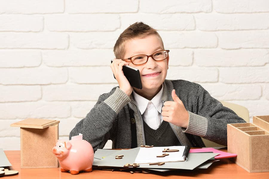 Kid with cell phone and piggy bank