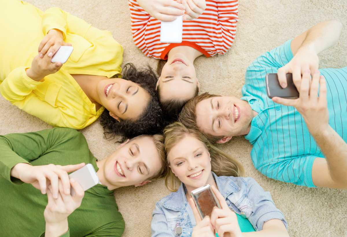 group of teens using phone | Best iPhone Apps Free Of Charge | best iphone apps free | must-have iphone apps