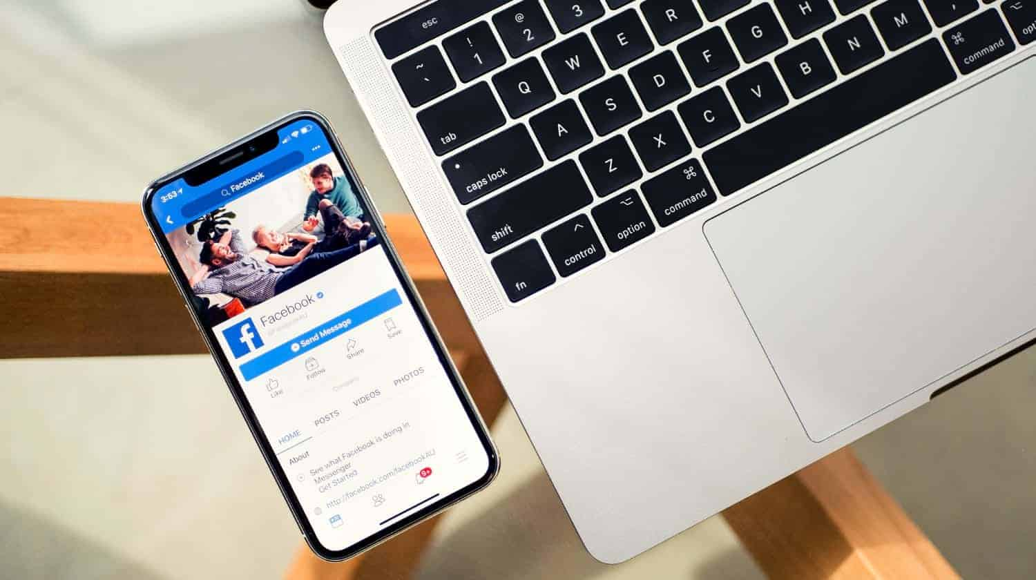 Featured | Facebook in smartphone with laptop | How To Change A Name On Facebook | Step By Step