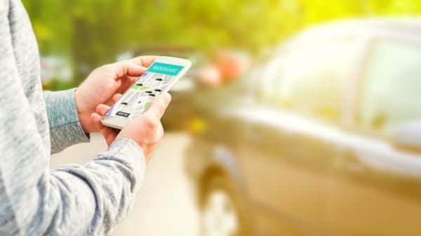 Featured | Rideshare taxi app on smartphone screen | Download These Rideshare Apps Today