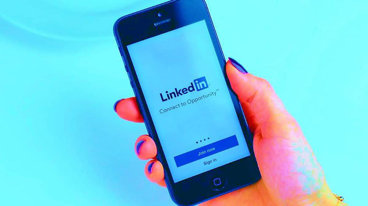 Holding mobile phone | How To Delete LinkedIn Account In Just A Few Easy Steps | Simple LinkedIn Guide