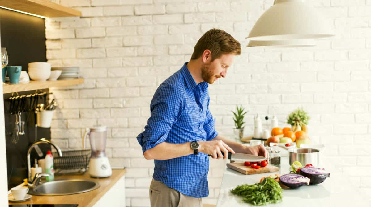 Young man chopping vegetables kitchen | The Ultimate Smart Home Systems Buying Guide