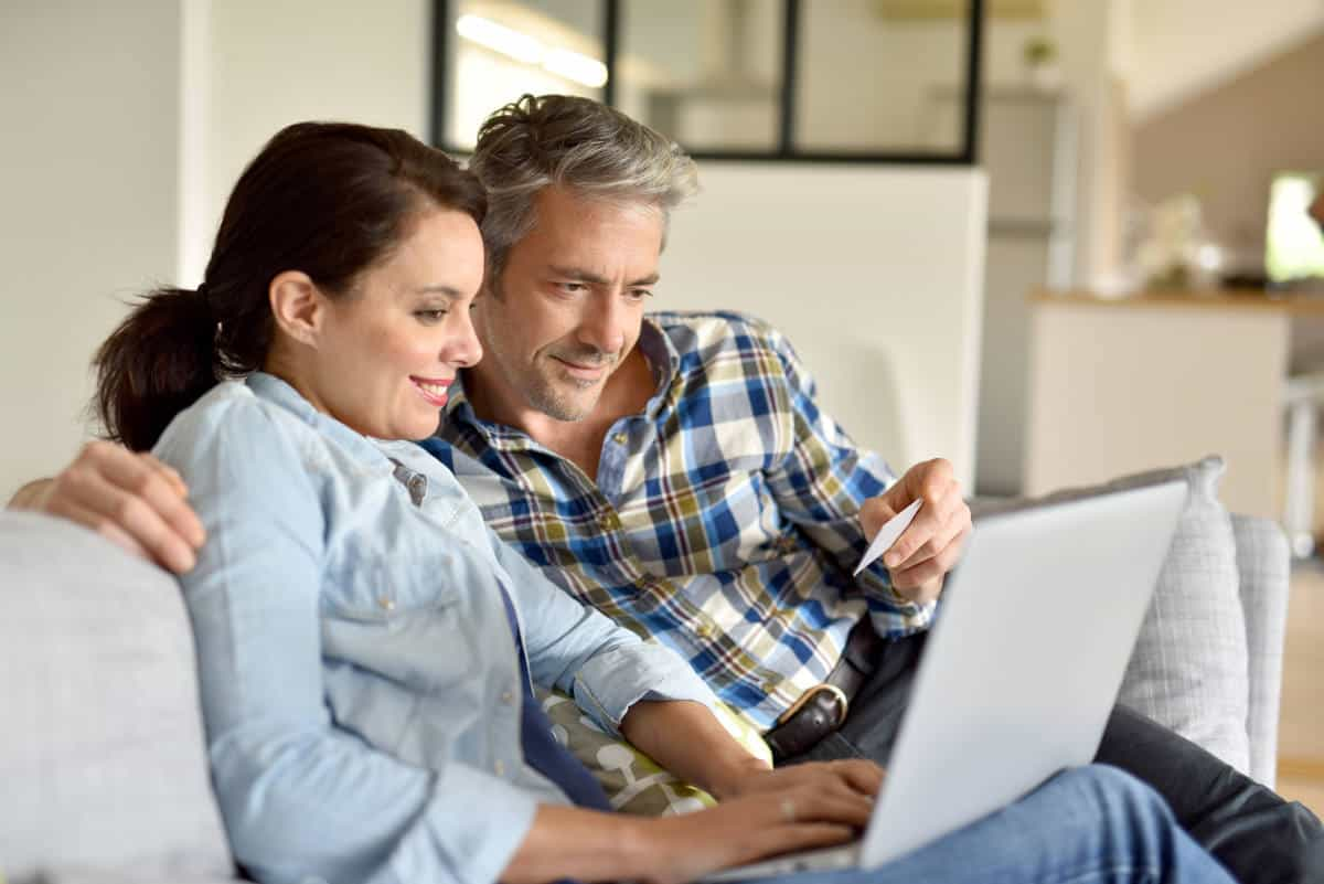 Couple sofa websurfing | StartYour Shopping Early. 'Black Friday' is Now a Season that Includes November and December so Start Shopping When You See Good Deals | Black Friday and Cyber Monday Shopping Survival Tips