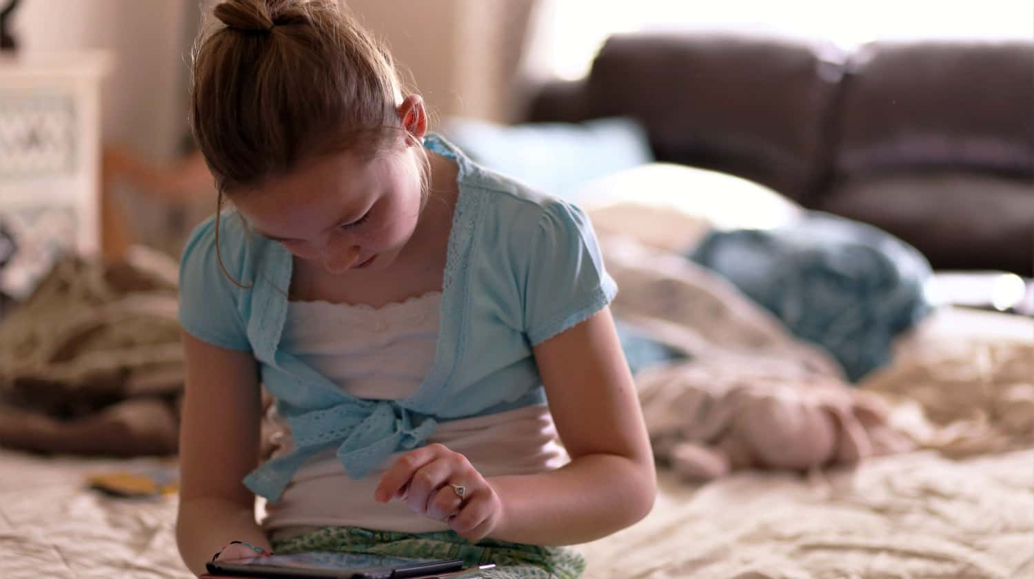 Feature | Girl sitting on bed holding tablet | Best eBooks on Kindle for Kids