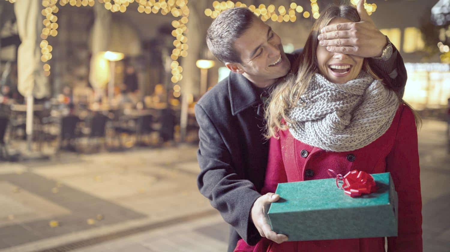 Feature | man keeping his girlfriends eyes close | Best Low-Priced Tech Gifts Anyone Will Love
