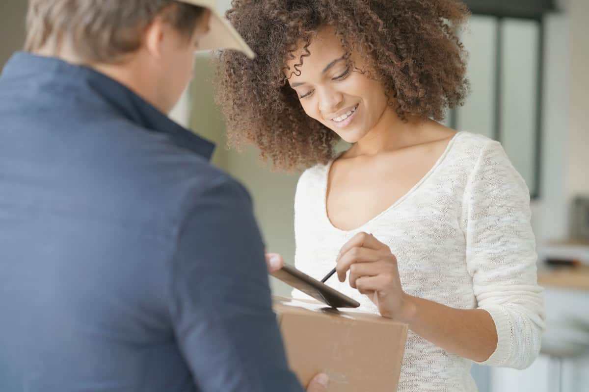 Mixed race woman receiving package from delivery man | Money-Making Side Hustles | Which One Is Best For You?