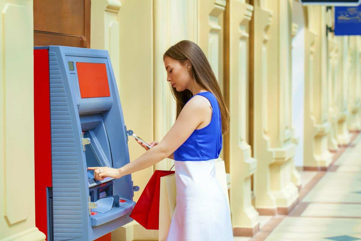 woman withdrawing money | Unconventional Ways to Save Money