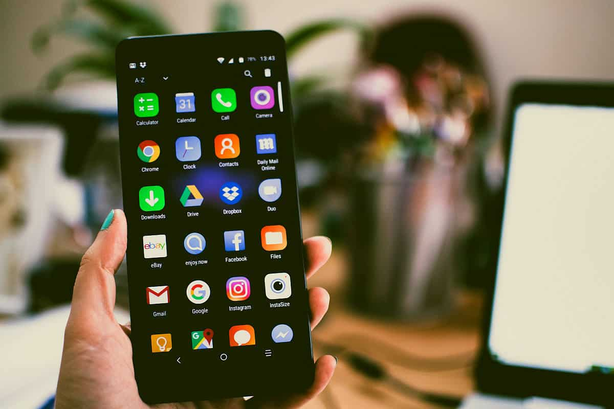 holding a mobile phone showing app icons | Tech Resolutions For The New Year