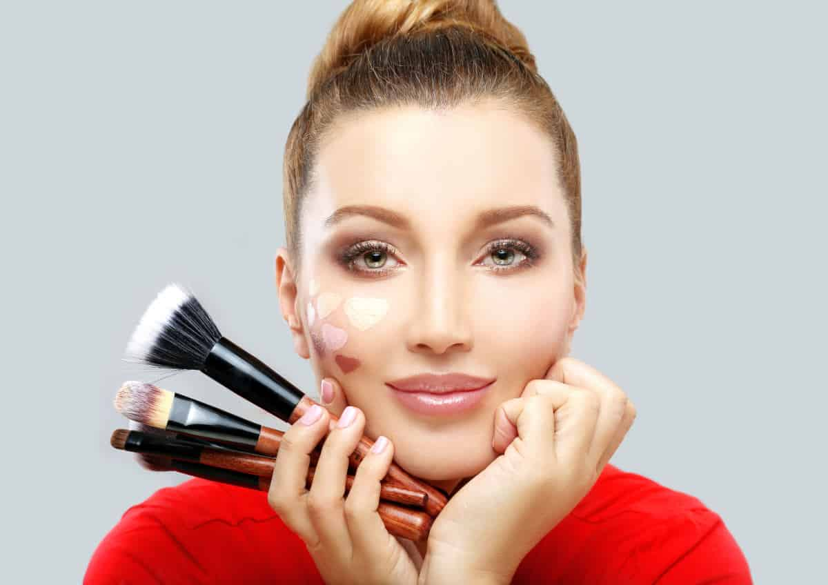 Beautiful woman holding makeup brush | There's An App For That | Phone Apps For Anything and Everything