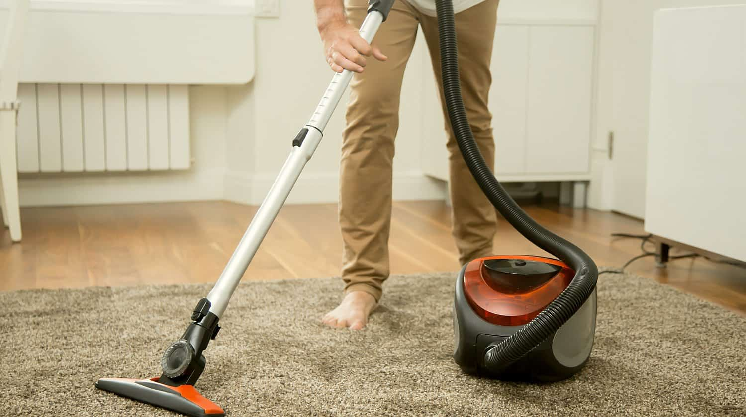Man Vacuum cleaning the carpet | Top Gadgets To Speed Up Your Spring Cleaning