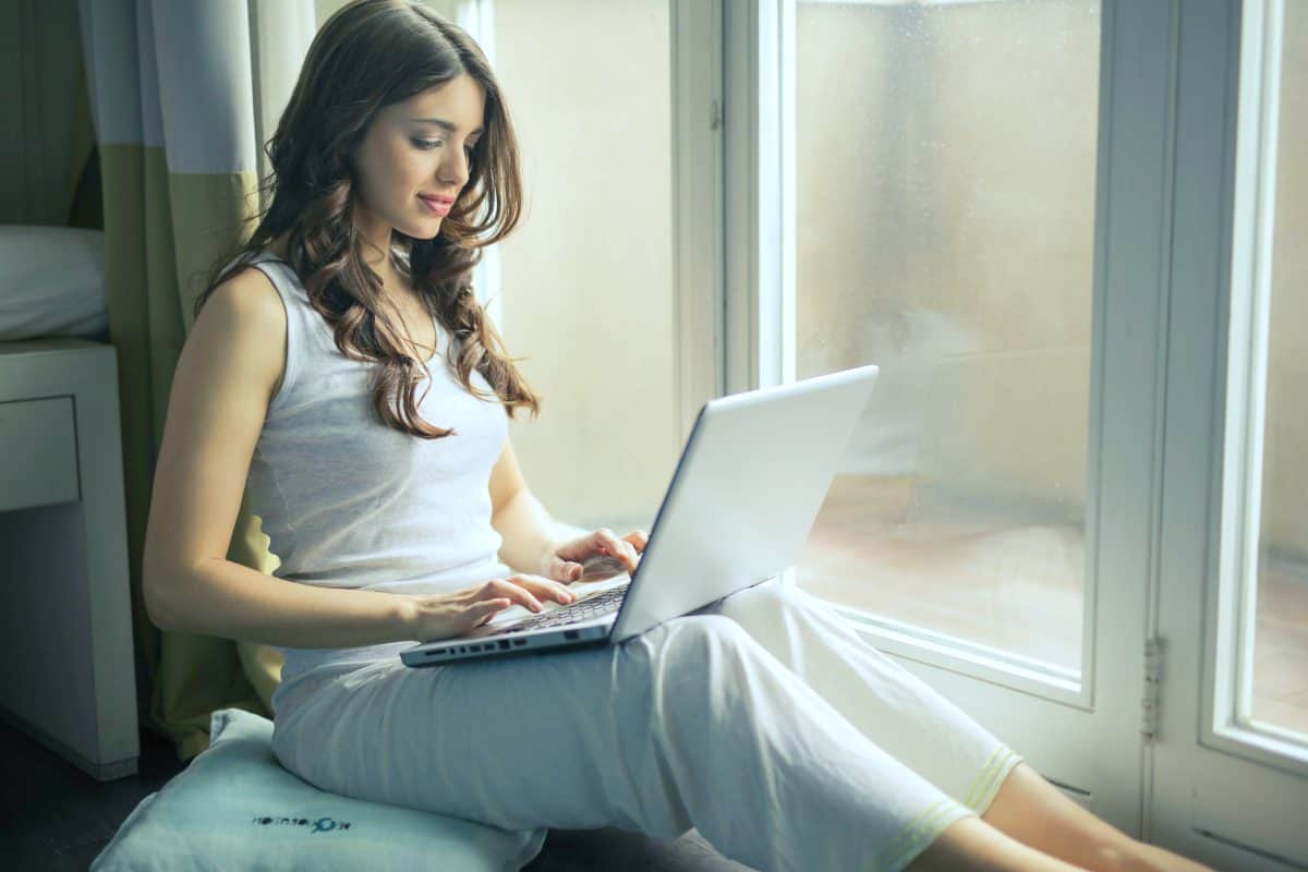 woman sitting by the window | Ways To Boost Your Home Wi-Fi Speed Without Spending A Dime | wifi speed test