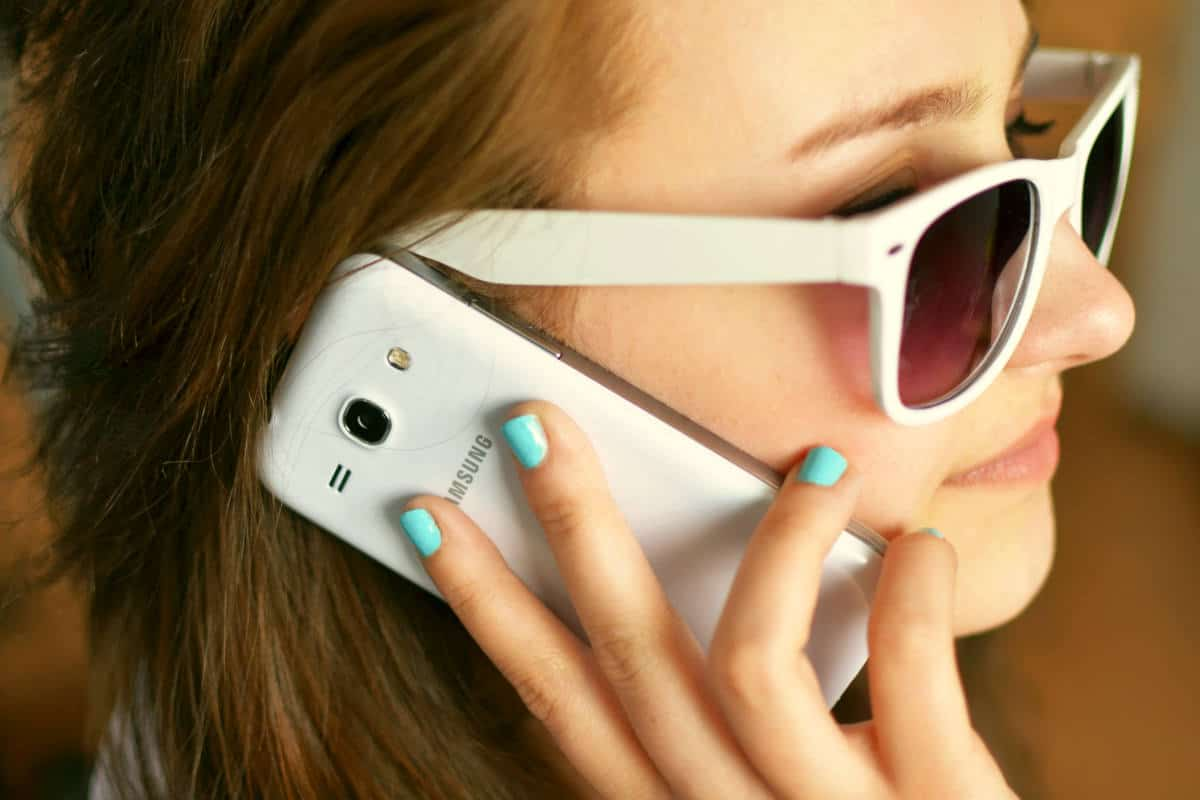 Person wearing sunglasses using smartphone | Cell Phone Rudeness Is Never Pretty | Ways You Are Being Rude With Your Cell Phone | rude cell phone manners