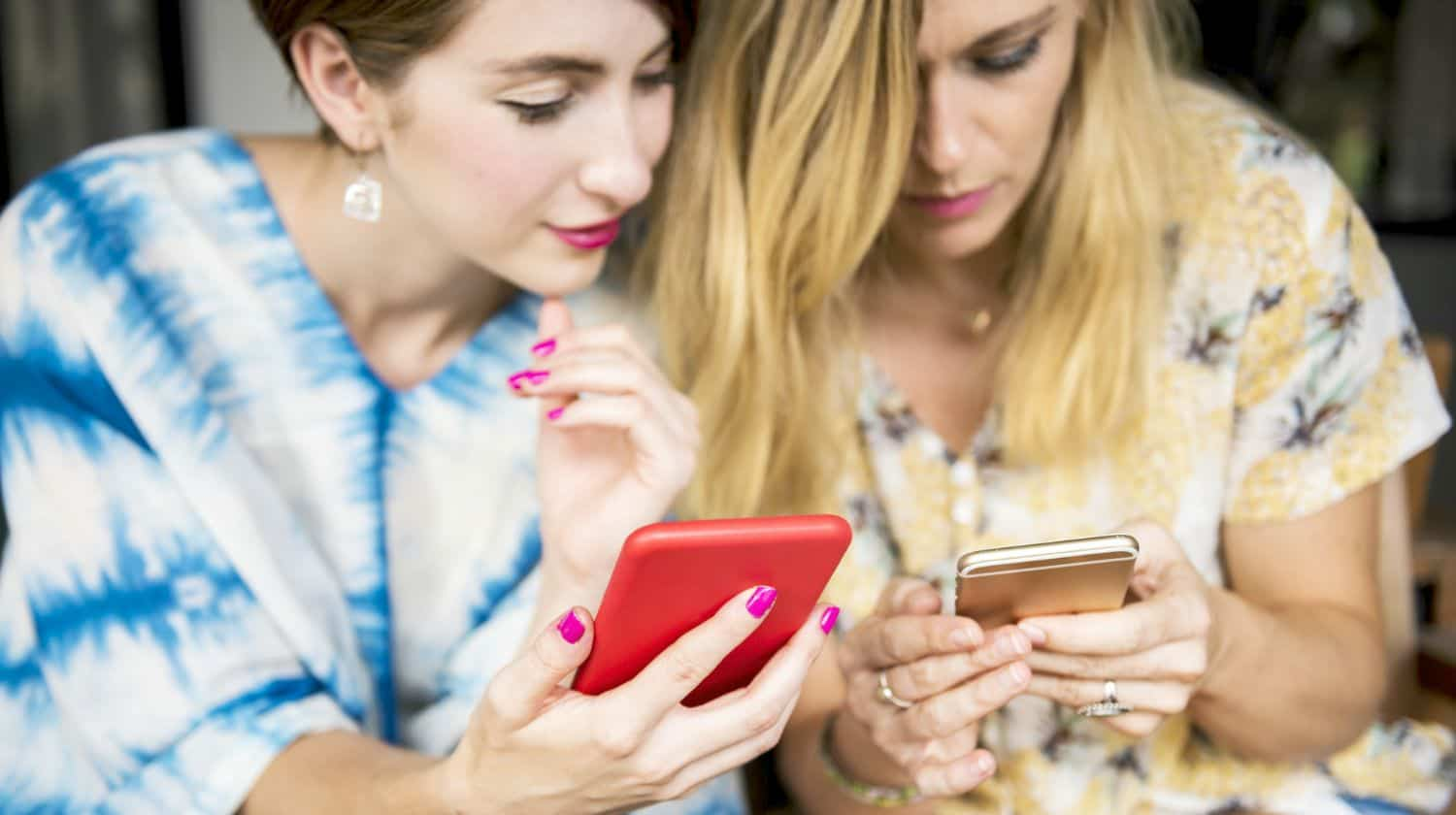 Feature   two women using phone   What Is A Mobile Hotspot? The Pros And Cons Unveiled   wi-fi hotspot   data   phone