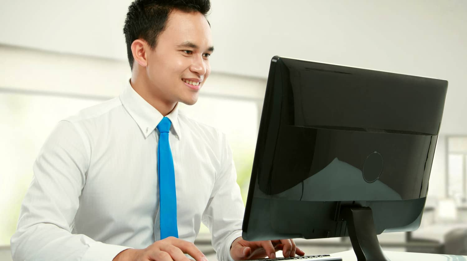 Feature | Portrait of a young business man smiling with computer in the office | How To Recover Unsaved Word Documents On Your Computer