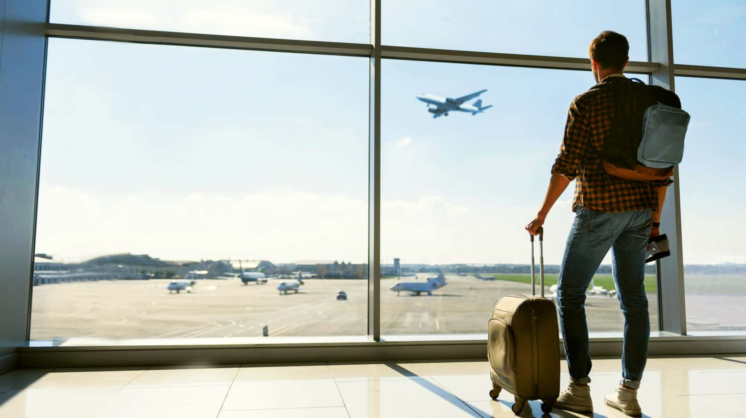 Feature | Young man is standing near window at the airport and watching plane before departure | Travel Tips For The Newbie International Traveler