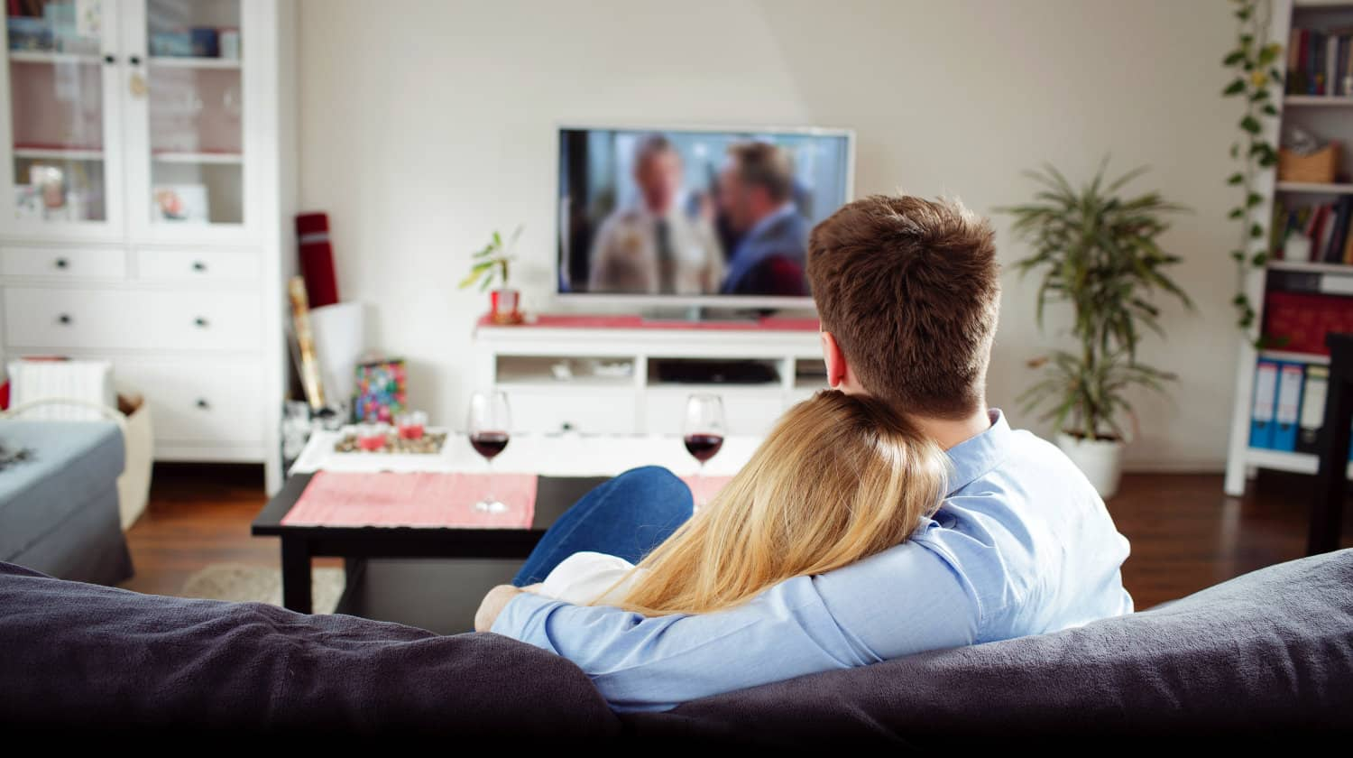 Feature | Back view of young couple enjoying themselves and watching tv on the sofa | Best Amazon TV Shows You Need to Watch ASAP