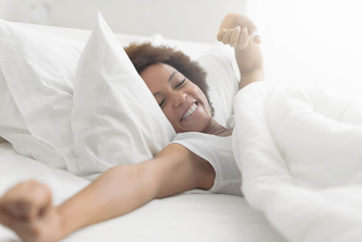 Beautiful woman waking up in her bed   Don't Dump Your Old Phone: 15 Things You Can Do With Your Old Smartphone