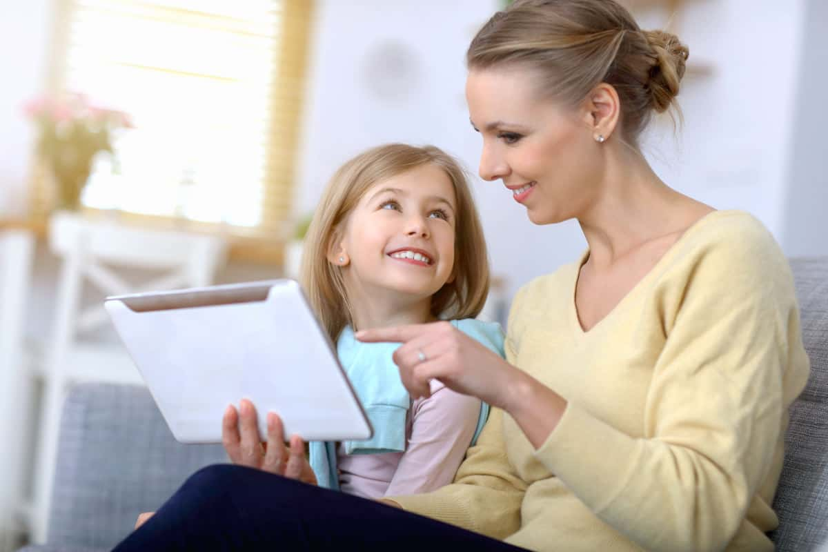 Little girl and her mom using tablet while sitting on sofa at home | Be More Tech Savvy With Tech Made Easy