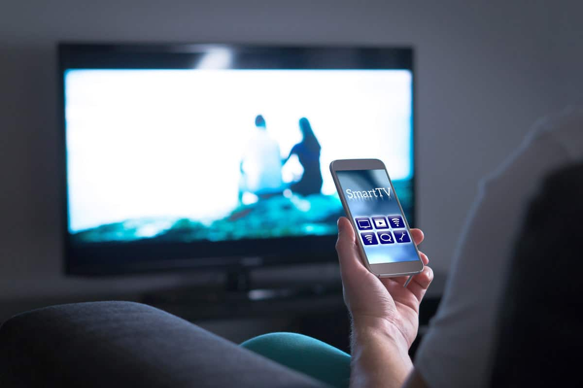 Man watching television and using smart tv remote control application on mobile phone | Don't Dump Your Old Phone: 15 Things You Can Do With Your Old Smartphone