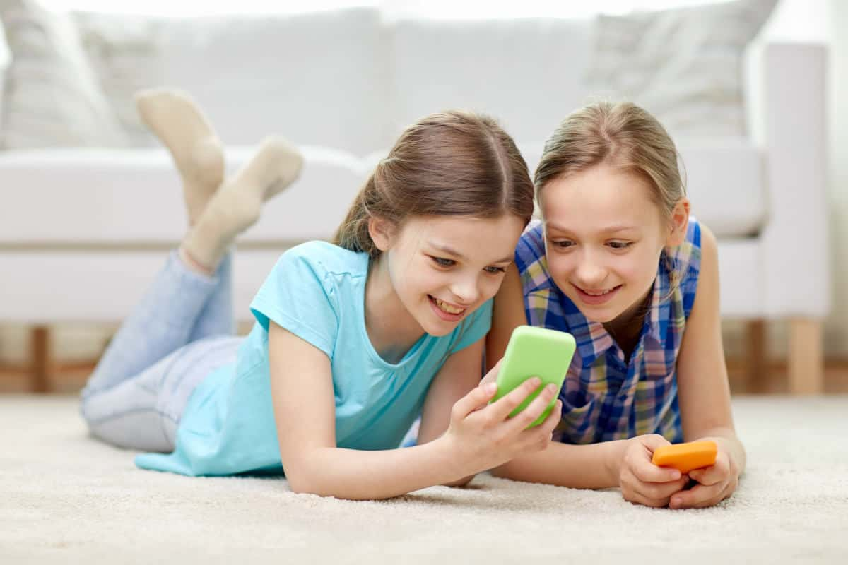 Happy little girls with smartphones lying on floor at home | Reasons To Monitor Your Kid's Cell Phone Use