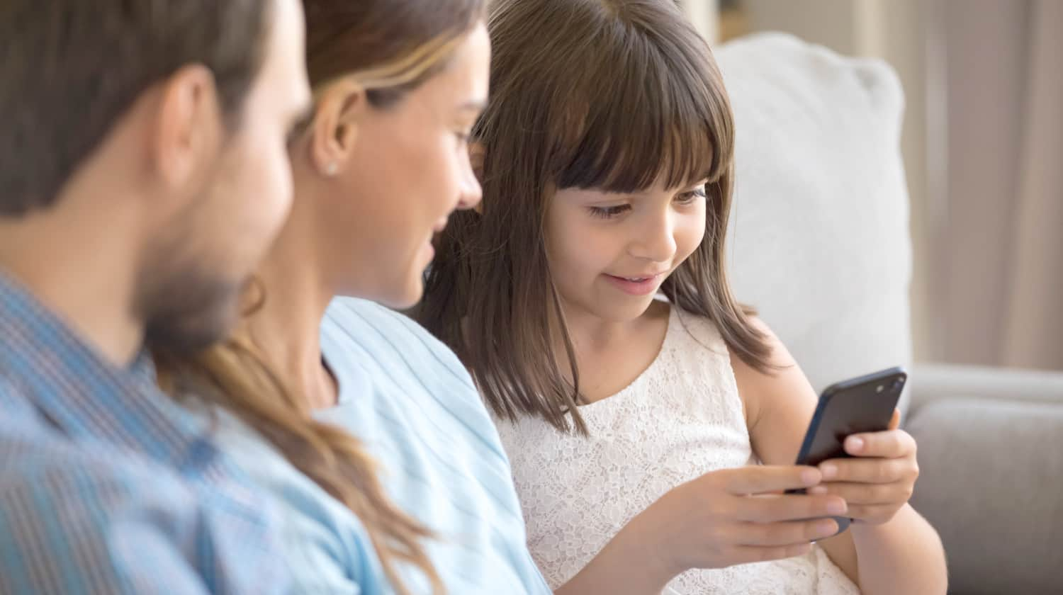 Feature   Smart funny preschooler girl sit on couch together with young parents   Best Free Parental Control App To Keep Your Kids Safe From Online Dangers