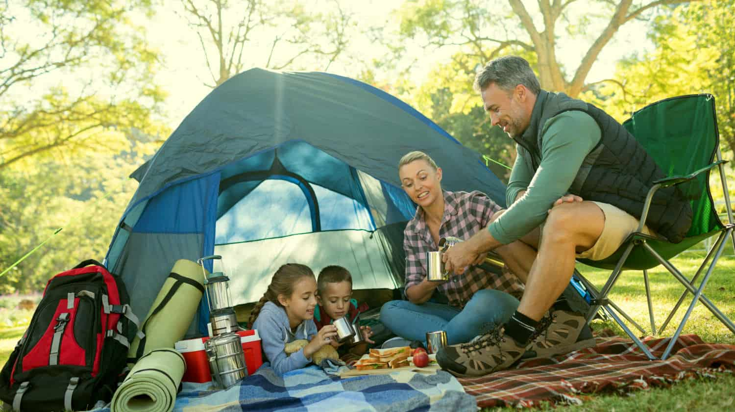 Feature | Family having snacks and coffee outside the tent at campsite | Cool Camping Must-Haves To Survive A Weekend Outdoors