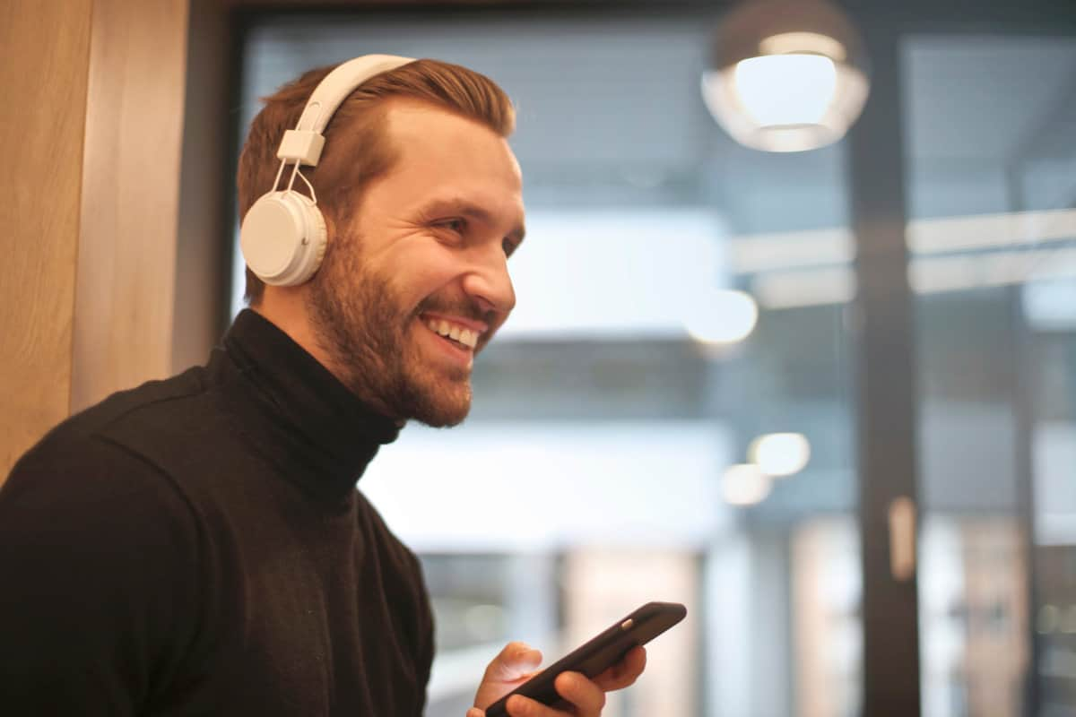 Man wearing white headphones | How Not To Go Over Your Data Cap
