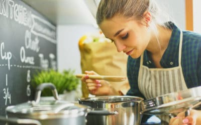 Feature | Young woman cooking in her kitchen standing near stove | Smart Kitchen Decor And Gadgets That Will Make Cooking More Fun