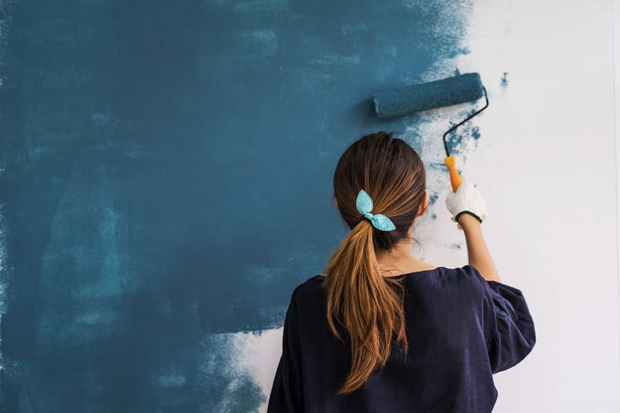 Woman painting interior wall