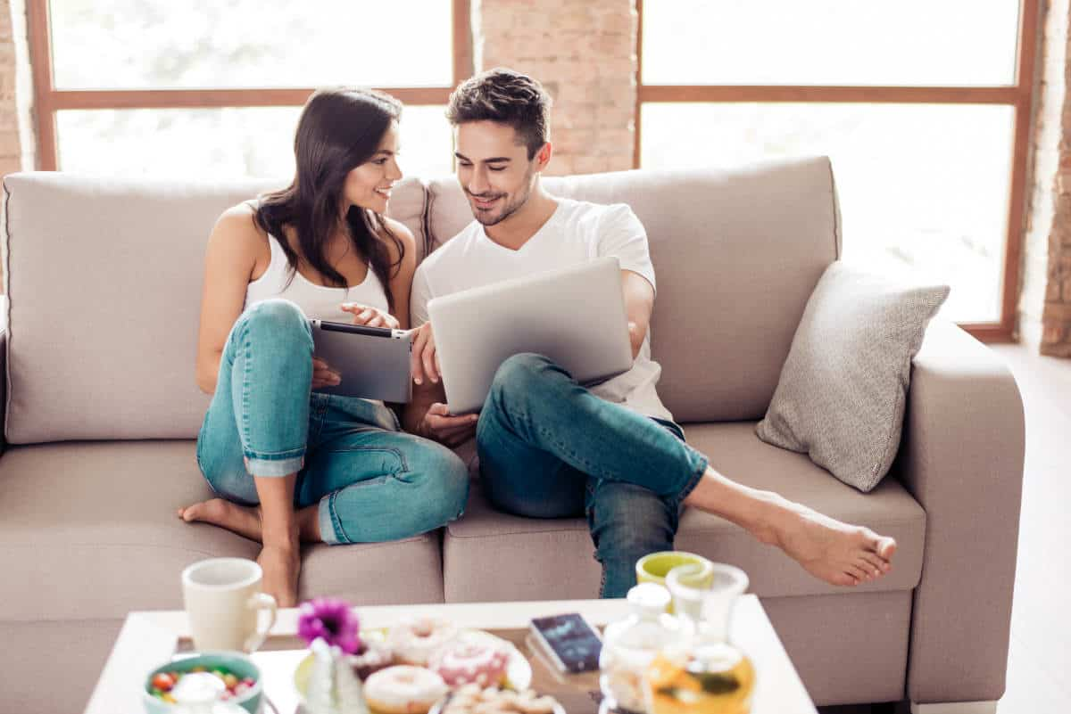 Cheerful happy couple is doing online shopping in internet at home indoors | How to Speed Up Wi-Fi at Home | how to speed up wifi on laptop