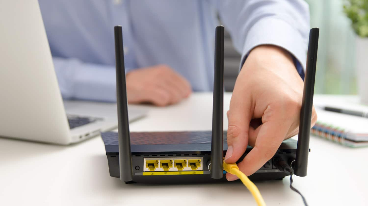 Man plugs Ethernet cable into router | How to Speed Up Wi-Fi at Home | how to boost wifi signal | Featured