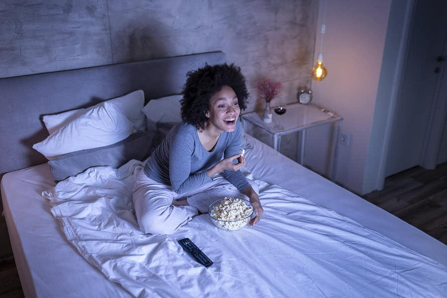 Woman eating popcorn on bed watching movie